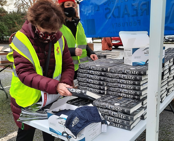 A woman prepares books to give away for a library event