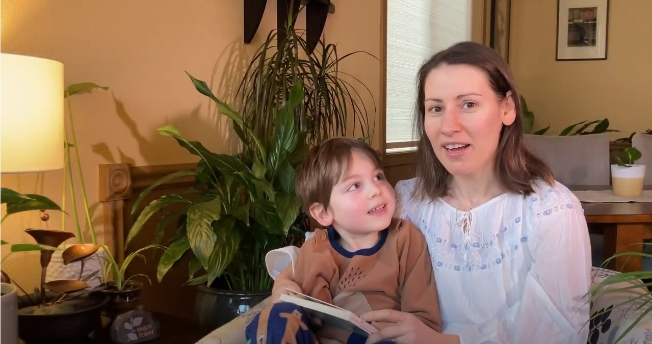 A mother and young son sit together to read a picture book in English and Spanish