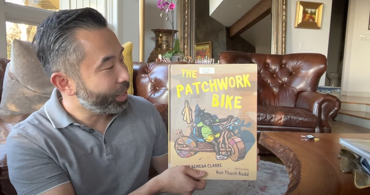 A man reads out loud from a storybook with a yellow bike on the cover