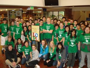 group of 50 teens in green shirts in the library